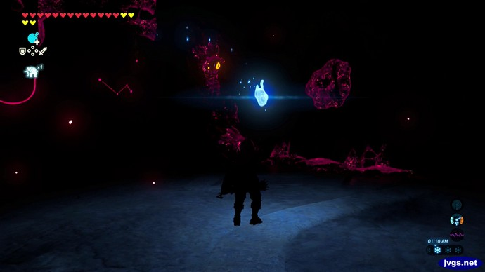 Link holds a blue flame with a torch inside the darkness of Rudania in Zelda BOTW.