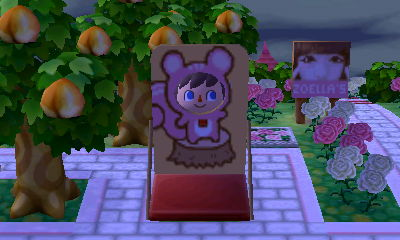 A mouse on the face-cutout standee and a custom-design sign leading to Zoella's house in Pastelia.